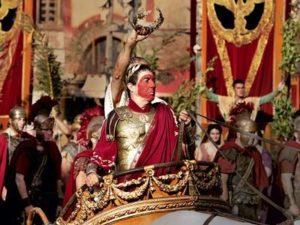 Triomphe de César dans la série Rome. Un esclave se tient derrière lui.